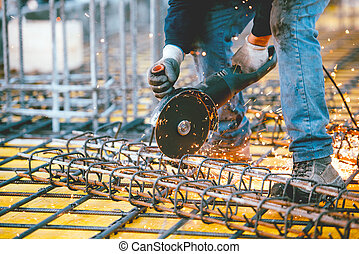 worker using an angle grinder for cutting steel, making...