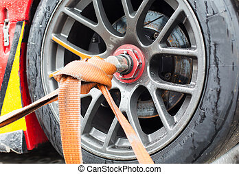 close up of race car wheel with tow rope tied to -...