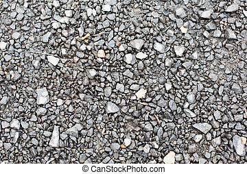 close up of gray macadam stones on ground - background and...