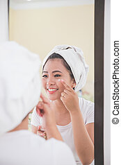 Woman applying skincare lotion into her face