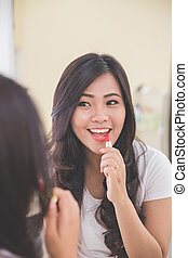 Woman applying red lipstick on her lips, look at the mirror