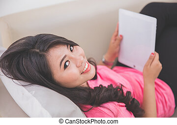 Woman laying on a couch using a tablet pc