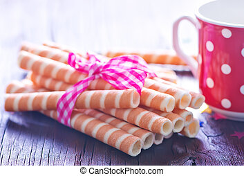 wafer tubes and milk in cup on a table