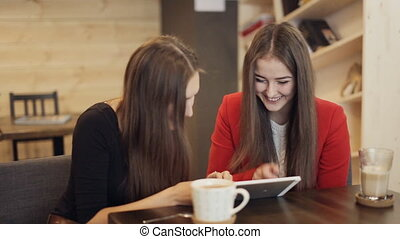 Two happy girlfriends with tablet smile in cafe - Two...