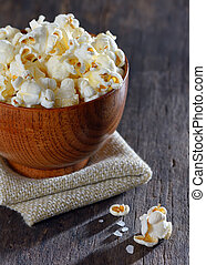 Salty popcorn on wooden table