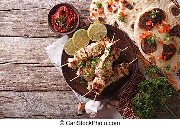 Chicken tikka on skewers, flat bread and chutney. Horizontal...