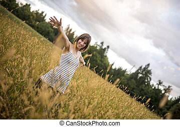 Young woman standing in the middle of autumn meadow with high golden grass smiling