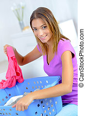 Young lady sorting laundry