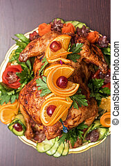 Whole roasted chicken with vegetables and fruits on wooden...