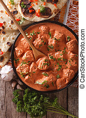 tikka masala chicken and naan flat bread close-up. vertical...