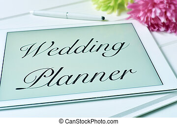 text wedding planner in the screen of a tablet - the text...