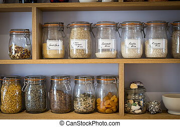 Storage jars - Labelled storage jars on shelves with rices...