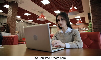 Woman working on modern laptop in cafe - Woman working on...