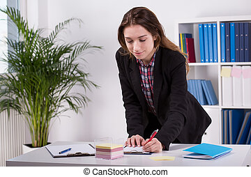 Female worker writes down ideas - Picture of a female worker...