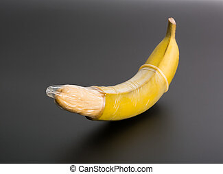 Big banana with condom on grey background