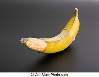 Big banana with condom on grey background