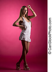 Sexy girl posing in nightgown, on pink background