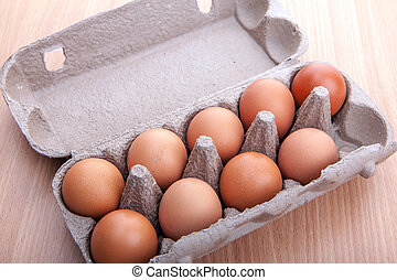 brown eggs in egg carton on kitchen table - brown eggs in...