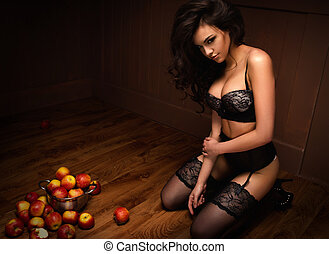 Sexy beautiful girl sitting on a floor with apple