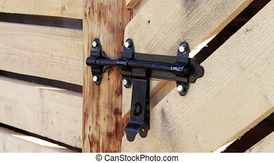 Lock shutter in the wooden door. - The man opens the shutter...