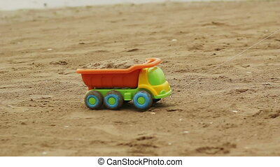 Childs Car Toy - Toy cars being dragged through the sand
