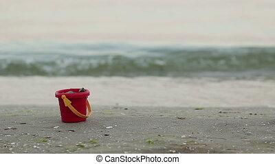 Childs Bucket at Beach - Childs bucket at beach and sea on...