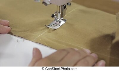 female hands sewing fabric on sewing machine - Close-up...
