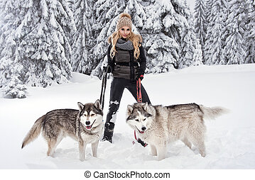 Happy young woman playing with siberian husky dogs in winter...