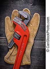 Leather protective glove monkey wrench on wooden board