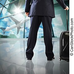 Airplane taking off - Businessman with suitcase looks...