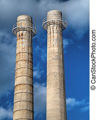 These are two factory chimneys on blue sky.
