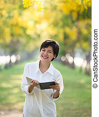 portrait of young asian woman and book in hand rising hand...