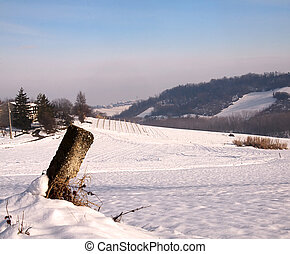 Milestone with snow - Landscape of a snow-covered hill with...