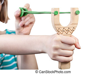 girl pulls green rubber band of wooden slingshot