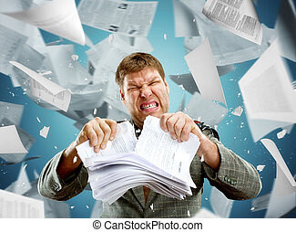 Stressed businessman tearing out stack of paper