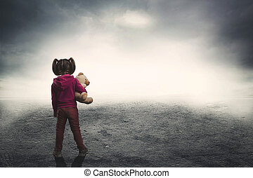Little girl with toy bear in the darkness - Little girl...