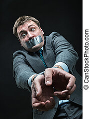 Man with mouth covered by masking tape - Man with mouth and...
