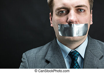 Man with mouth covered by masking tape preventing speech,...