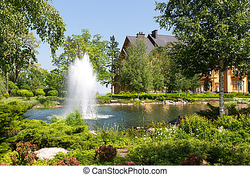 Beautiful lake in green spring park with fountain