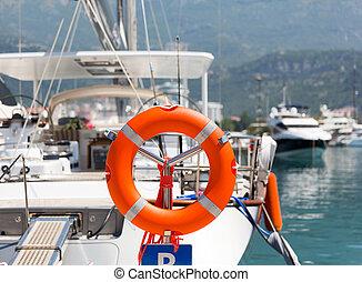 Lifebuoy in sea port against luxury yacht