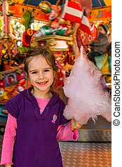 child with cotton candy on kirtag - a girl has fun and look...