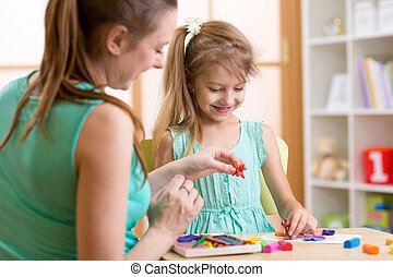 Happy child and mother sitting at table and playing with...