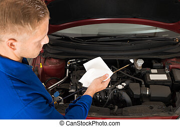 Mechanic Checking Oil Level In Car Engine - Close-up Of A...