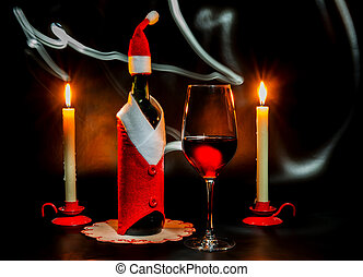 Christmas still life with a wine bottle, candles and a wine glass