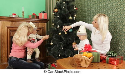 Two Happy Women With Babies Decorating Christmas Tree