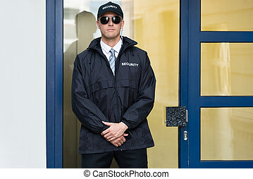 Male Security Guard Standing At The Entrance - Young Male...