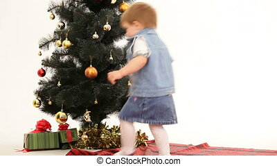 Little Girl Taking Gifts Under Christmas Tree - Little girl...
