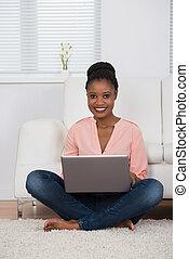 Woman Sitting On Carpet Using Laptop