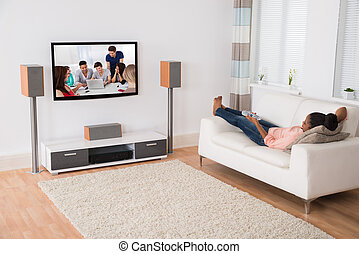 Woman Watching Television While Lying On Sofa - Young...