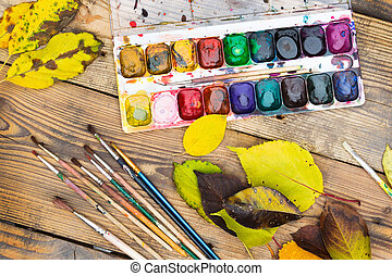 Plastic paint palette with paint, brushes and yellow leaves...